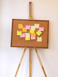 A per fare lista con la carta di Post-it sulla bacheca del sughero immagini stock