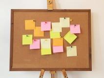 A per fare lista con la carta di Post-it sulla bacheca del sughero immagine stock libera da diritti