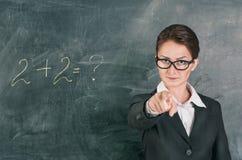 Per la matematica d'istruzione dell'insegnante della donna ed indicare su qualcuno fotografie stock libere da diritti