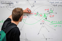 Per la matematica di scrittura dell'allievo sul whiteboard Immagini Stock