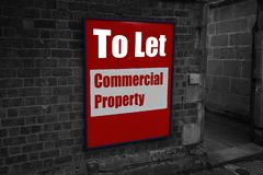 per lasciare con la proprietà commerciale scritta su un segno allegato ad un muro di mattoni immagine stock libera da diritti