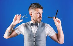 per tagliare o radersi Uomo barbuto con il rasoio e forbici in retro parrucchiere Barbiere che tiene gli strumenti d'annata del b immagine stock libera da diritti
