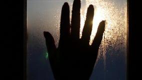 Per toccare la mano per cadere sul vetro contro il contesto di bello tramonto, lasci un handprint con le gocce delle strisce video d archivio
