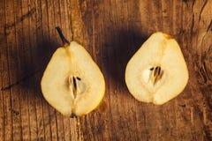 Pera amarela cortada na tabela de madeira Imagens de Stock Royalty Free