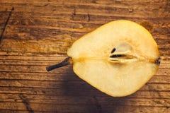Pera amarela cortada na tabela de madeira Fotografia de Stock Royalty Free