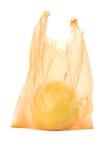 Pera amarela no saco de plástico alaranjado Fotos de Stock Royalty Free