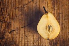 Pera amarilla cortada en la tabla de madera Imágenes de archivo libres de regalías