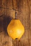 Pera amarilla en la tabla de madera Foto de archivo