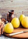 Pera amarilla en un tablero de madera, palillos de canela, foco selectivo Foto de archivo