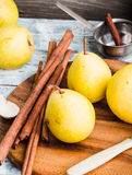 Pera amarilla en un tablero de madera, palillos de canela, foco selectivo Foto de archivo libre de regalías