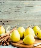 Pera amarilla fresca en un tablero de madera, palillos de canela, aún vida Imagen de archivo libre de regalías
