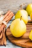 Pera amarilla fresca en un tablero de madera, palillos de canela, aún vida Imagenes de archivo