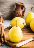 Pera amarilla fresca en un tablero de madera, palillos de canela, aún vida Foto de archivo