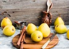 Pera amarilla fresca en un tablero de madera, palillos de canela, aún vida Fotografía de archivo libre de regalías