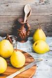 Pera amarilla fresca en un tablero de madera, palillos de canela, aún vida Foto de archivo libre de regalías