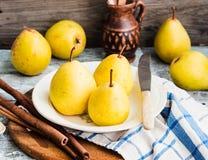 Pera amarilla fresca en un tablero de madera, palillos de canela, aún vida Fotos de archivo