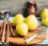 Pera amarilla fresca en un tablero de madera, palillos de canela, cierre para arriba Foto de archivo libre de regalías