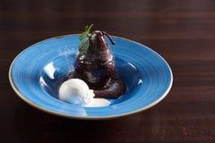 A pera caçada com molho de chocolate serviu com uma colher do cre do gelo imagem de stock royalty free