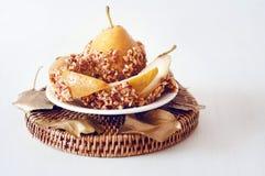 A pera caramelizada mergulhou com os amendoins decorados com licença dourada Fotografia de Stock Royalty Free