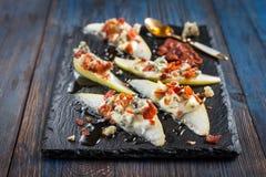 Pera con gorgonzola, bacon e miele su un fondo nero Fotografie Stock Libere da Diritti