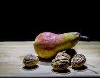 Pera con i dadi su una tavola di legno immagine stock