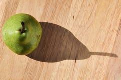Pera con la sombra en tabla de cortar Fotografía de archivo