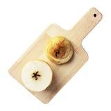 Pera cortada en un tablero de madera aislado en blanco Imagen de archivo
