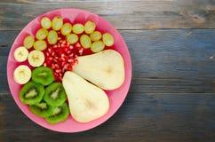 Pera del preparato della frutta, kiwi, uva, banana, melograno su un di legno Immagini Stock