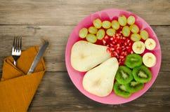 Pera del preparato della frutta, kiwi, uva, banana, melograno su un di legno Immagine Stock Libera da Diritti
