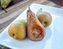 A pera derretida e fresca frutifica em uma placa branca fotografia de stock