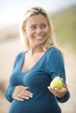 Pera a disposición de la mujer embarazada sonriente imagen de archivo libre de regalías