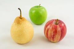 Pera e due mele su un fondo bianco Fotografia Stock