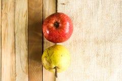 Pera e maçã de dois frutos com textura do fundo da madeira e da esteira Imagens de Stock Royalty Free