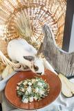 Pera ed insalata della rucola con i pinoli vicino al bello coniglio bianco Immagine Stock