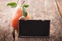Pera fresca con una pizarra en blanco Foto de archivo libre de regalías