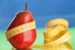 Pera fresca vermelha com a fita no fundo, saúde e fotografia de stock royalty free