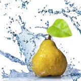 Pera gialla con la spruzzata dell'acqua e del foglio isolata Fotografia Stock