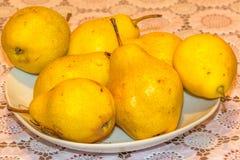 Pera gialla su un piatto Immagini Stock