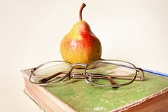 Pera, libro y vidrios Imagen de archivo libre de regalías
