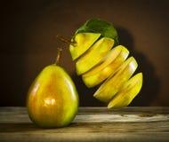Pera matura affettata fresca con le foglie che appendono nell'aria Fotografia Stock