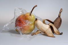 Pera matura arancio luminosa in film trasparente ed in banana matura e mezzo sbucciata toccantesi, frutta fresca, una metafora de Immagini Stock
