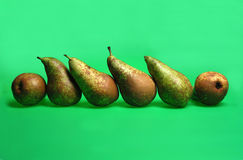 Pera, peras en fila en el estudio con el fondo verde Fotografía de archivo libre de regalías