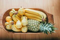 Pera, plátano y piña en una cesta de madera Fotografía de archivo