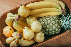 Pera, plátano y piña en una cesta de madera Imagenes de archivo