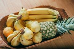 Pera, plátano y piña en una cesta de madera Imagen de archivo libre de regalías