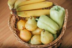 Pera, plátano y piña en una cesta de madera Foto de archivo