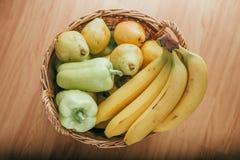 Pera, plátano y pimienta verde en una cesta Fotografía de archivo