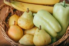 Pera, plátano y pimienta verde en una cesta Foto de archivo libre de regalías