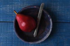 Pera roja con el cuchillo en azul Foto de archivo