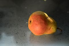 pera Rosso-gialla su una tavola di pietra alla bella luce primo piano della pera e controsoffitto grigio del granito Fondo immagine stock